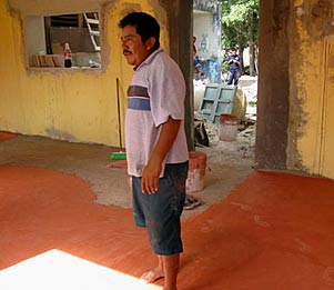 Graciano checking the new terracotta concrete floor at the Xcalacoop Child Care Center new classroom